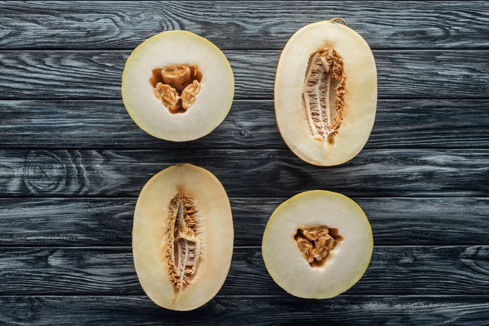 A picture of cantaloupe and honeydew's split open exposing their seeds. Sitting on a wooden background.