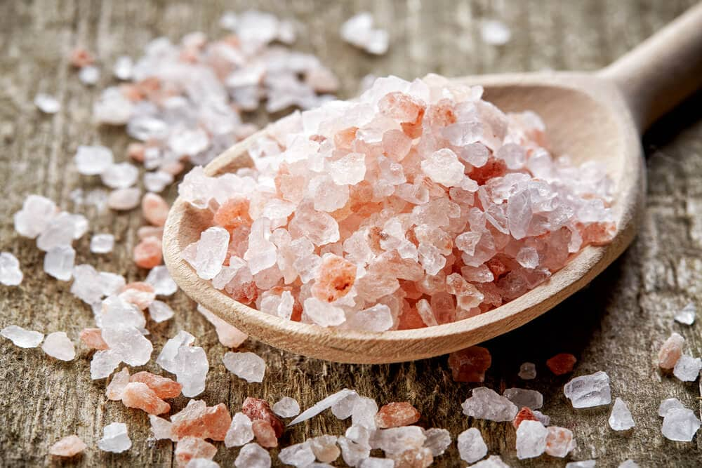 A picture of Himalayan sea salt in a wooden spoon and crystals laying beside it.