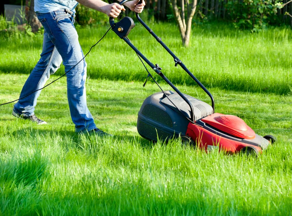 A man cutting tall grass with an electric lawn mower.