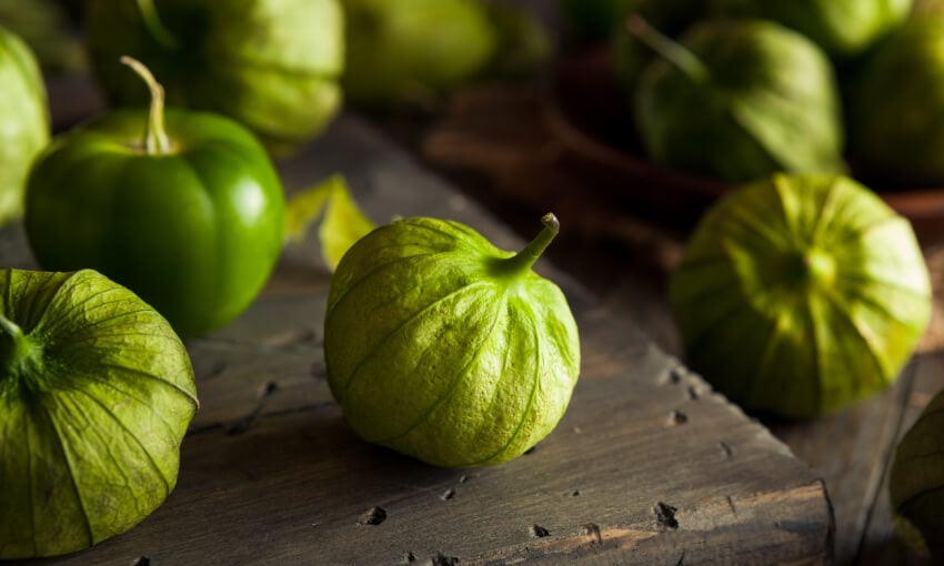A picture of tomatillos on a wood surface.