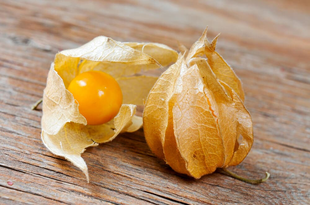 An image of ground cherries on a wood surface.
