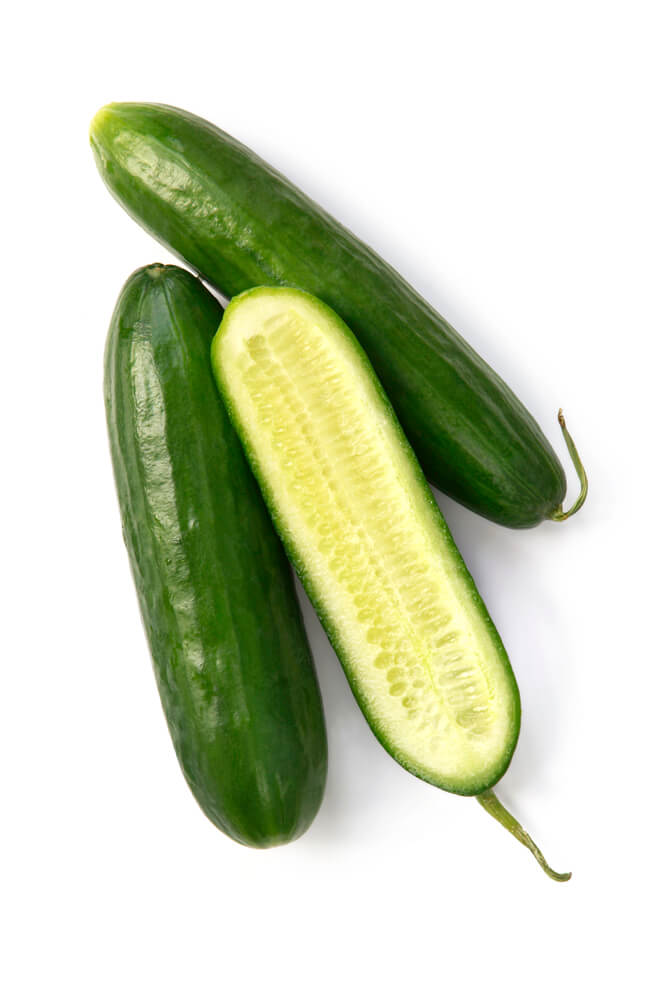 Lebanese cucumbers over a white background.